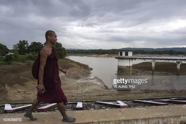 A Buddhist monk walks along a dam wall of Swar Chaung Dam showing decreased level of water after the collapse of the spillway at Swar township Bago...