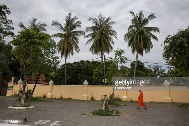 A Buddhist monk walks along a sidewalk in Phnom Penh Cambodia on Sunday July 29 2018 Cambodian Prime MinisterHun Senextended his...