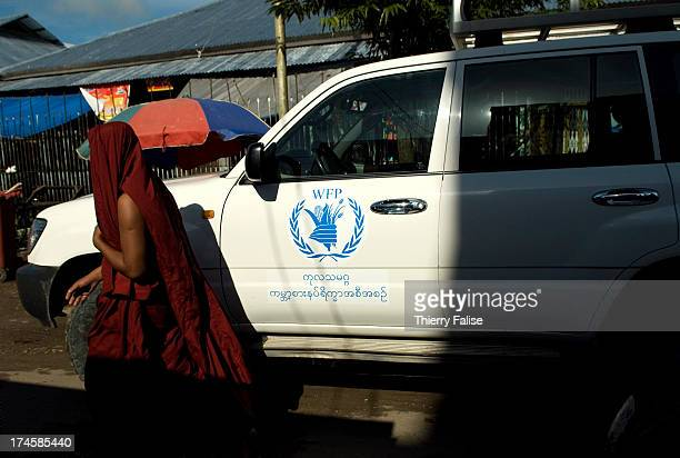 Buddhist monk walks by a car of the World Food Program team in Bogale a town which has become a hub for humanitarian organizations in the Irrawaddy...