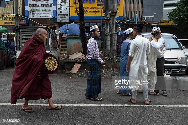 A Buddhist monk walks by Myanmar Muslims greeting one another outside the Narsapuri mosque to mark Eid alFitr in Yangon on July 7 2016 as the...