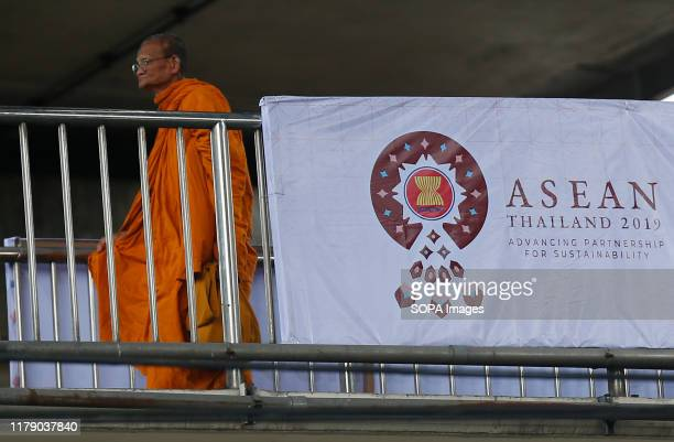 Buddhist monk walks past a banner welcoming the Association of Southeast Asian Nations leaders ahead of the 35th ASEAN Summit in Bangkok Thailand