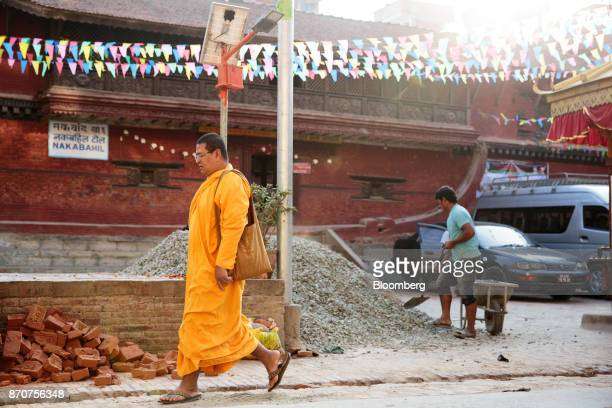 A Buddhist monk walks past a gravel pile of rocks in Lalitpur Kathmandu Valley Nepal on Wednesday Nov 1 2017 India and China have often jostled for...