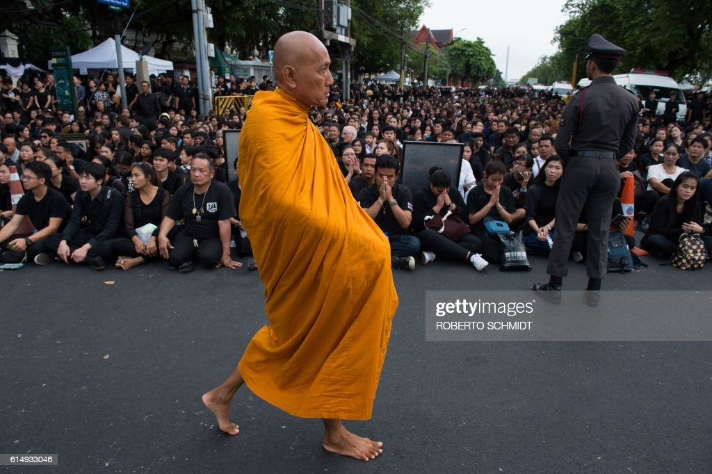 Buddhist monk walks past a large crowd clad in black gathered to pray for the late Thai King Bhumibol Adulyadej outside the Grand Palace in Bangkok on October 16, 2016. On his birthday Thais wore yellow, when he got sick they put on pink, and now that King Bhumibol Adulyadej has passed Bangkok's streets have turned monochrome in a extraordinary display of collective grief. / AFP / ROBERTO