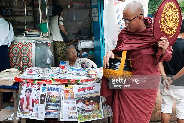 Buddhist monk walks past a newsstand selling newspapers showing pictures of Aung San Suu Kyi