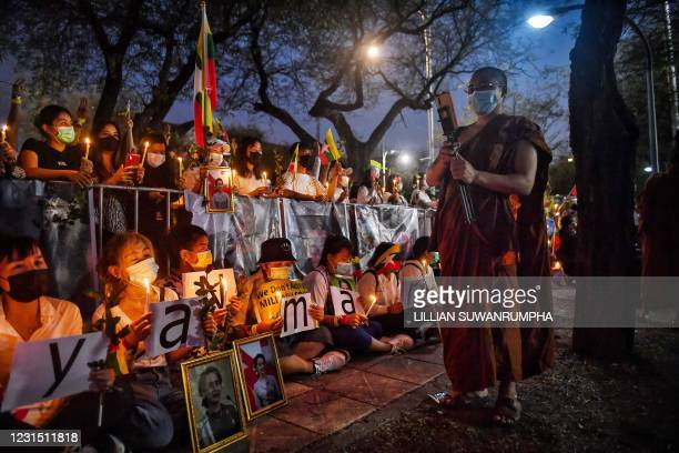 Buddhist monk walks past Myanmar migrants living in Thailand as they take part in a memorial in Bangkok on March 4, 2021 to honour those who died...