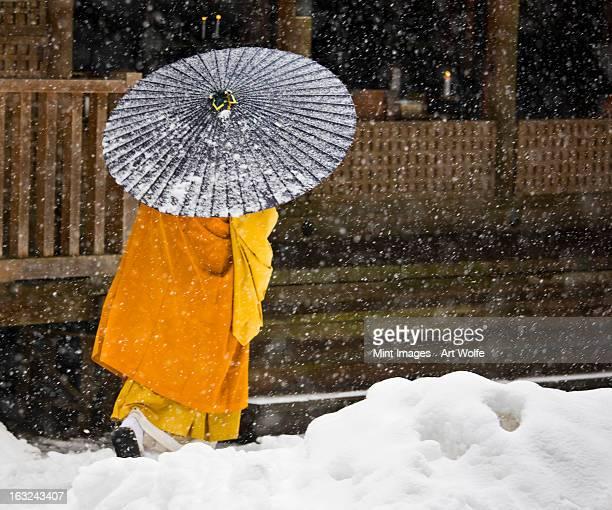 a buddhist monk walks through a snow flurry in koyasan, a centre for shingon esoteric buddhism. - shingon buddhismus stock-fotos und bilder