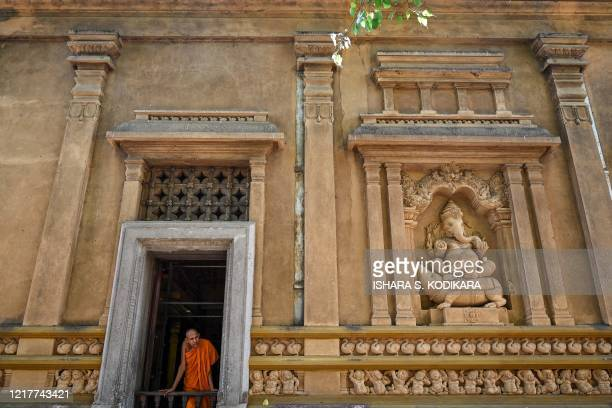 A Buddhist monk watches outside from an opening of the Kelaniya temple during the Poson Poya religious festival marking the arrival of Buddhism in...