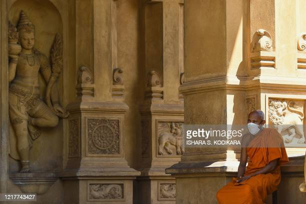 A Buddhist monk wearing a facemask sits at the Kelaniya temple during the Poson Poya religious festival marking the arrival of Buddhism in the island...