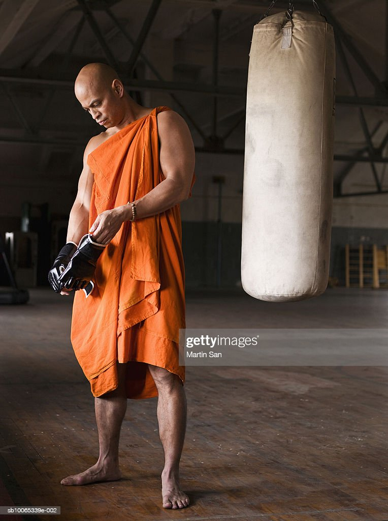 Buddhist monk wearing boxing glove in gym : Foto stock