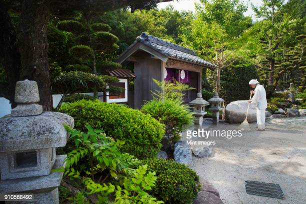 buddhist monk wearing white robe and cap standing outside a shrine in a temple garden, holding broom, sweeping floor. - shingon buddhismus stock-fotos und bilder