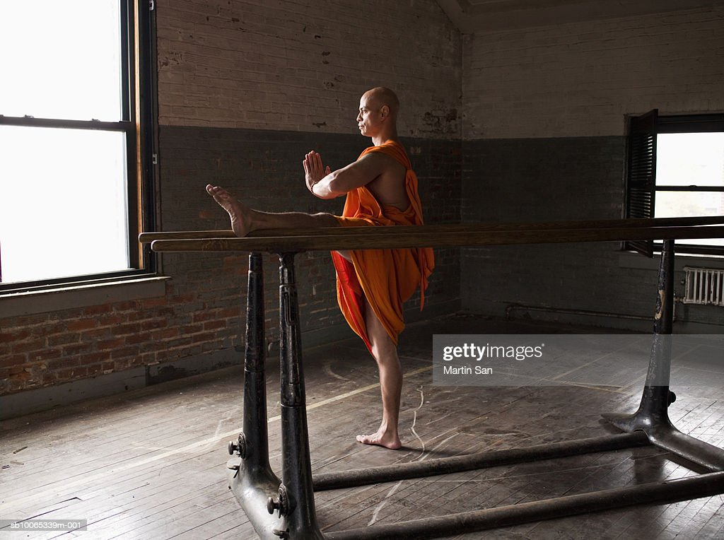 Buddhist monk with feet up on parallel bars praying : Foto stock