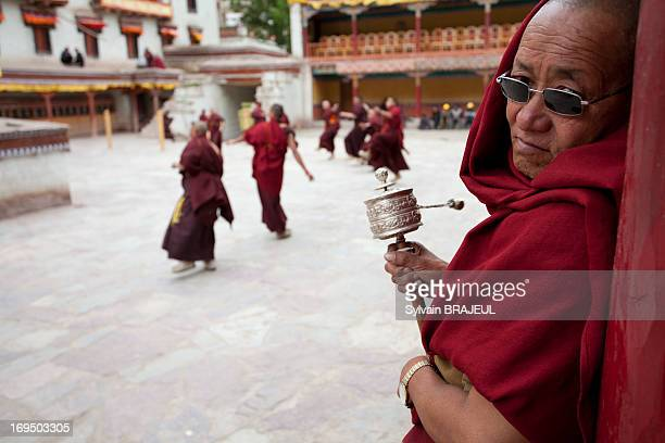 Buddhist monk with his wheeling prayer watching rehearsal of the dancing monks before Tse Chu Hemis festival in Ladakh Himalaya in North west India
