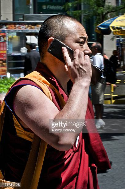 Buddhist monk with large cell phone on the streets of New York City, Midtown Manhattan