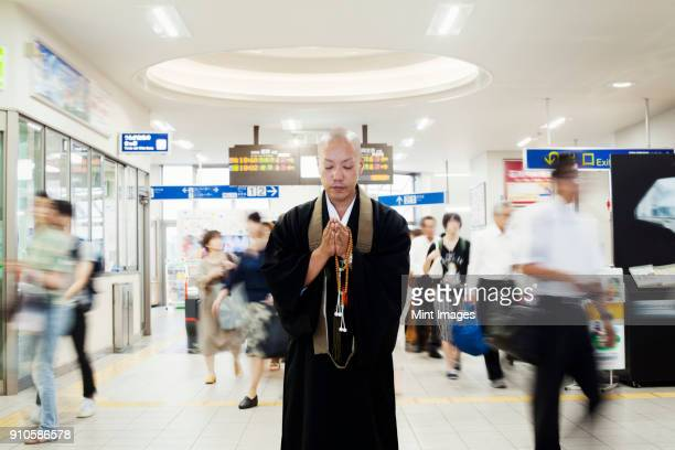 buddhist monk with shaved head wearing black robe standing inside a train station, holding mala, people walking past. - 僧 ストックフォトと画像