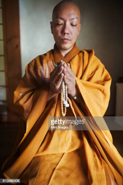 Buddhist monk with shaved head wearing golden robe kneeling indoors in a temple, holding mala, praying.