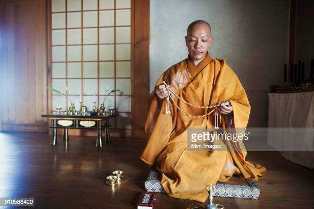 buddhist monk with shaved head wearing golden robe kneeling indoors in a temple, holding mala. - shingon buddhismus stock-fotos und bilder