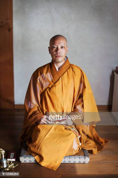 buddhist monk with shaved head wearing golden robe kneeling on floor in a temple, holding mala, looking at camera. - 僧 ストックフォトと画像