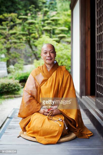 Buddhist monk with shaved head wearing golden robe sitting on floor outdoors, holding mala, smiling at camera.