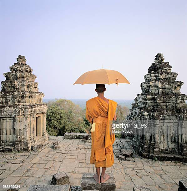 buddhist monk with umbrella standing atop angkor wat - monk stock pictures, royalty-free photos & images