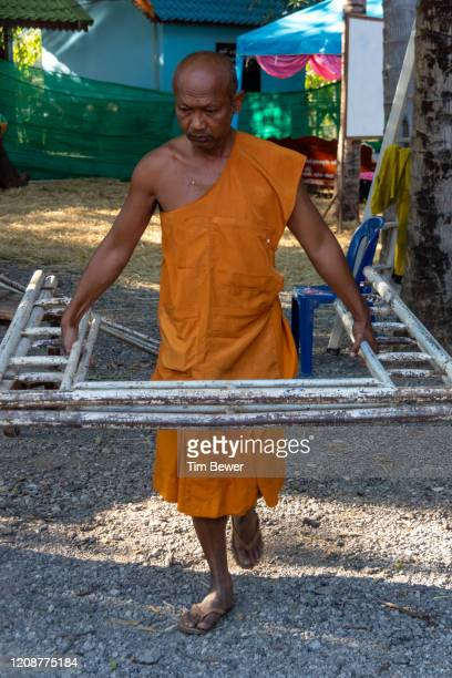 buddhist monk working. - tim bewer stock pictures, royalty-free photos & images