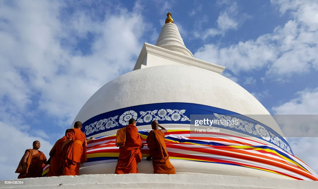 Buddhist  monks adorning the Thuparama dagoba with the Buddhist flag, Sri Lanka : Stockfoto