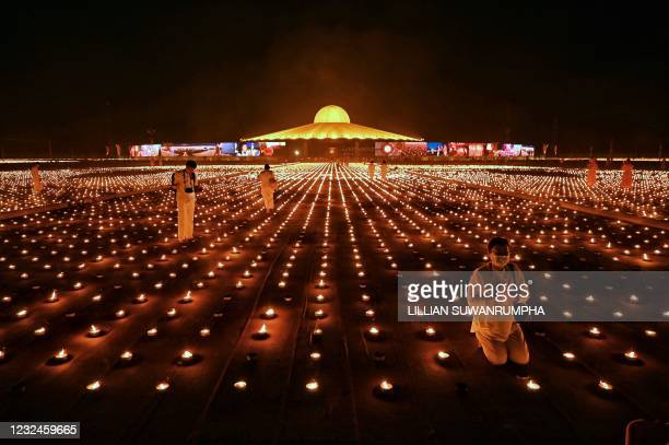 Buddhist monks and devotees take photos with 330,000 candles during an attempt to break the Guinness World Record for the largest flaming image...
