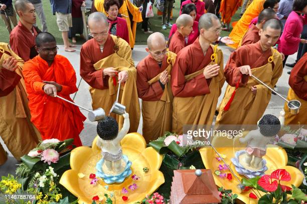 Buddhist monks and nuns from various Buddhist sects bathe statues of the Child Buddha during the festival of Vesak in Mississauga, Ontario, Canada....