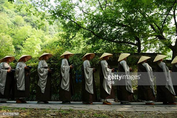 Buddhist monks and nuns of Lingyin Temple walk to receive Buddhists's offerings during a charity event on Monday to celebrate the birth of Sakyamuni...