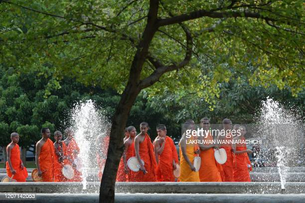 Buddhist monks arrive to take part in a special prayer ceremony for the relief from the spread of the COVID19 novel coronavirus at the Independence...