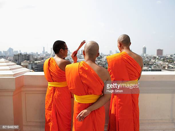 buddhist monks at wat saket overlooking bangkok - hugh sitton stock-fotos und bilder
