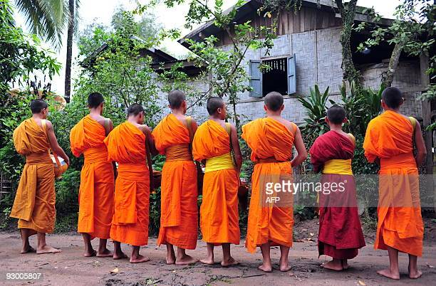Buddhist monks bless a local house after reciving alms from its residents in Luang Namtha northern Laos on October 14 2009 About 60% of the...