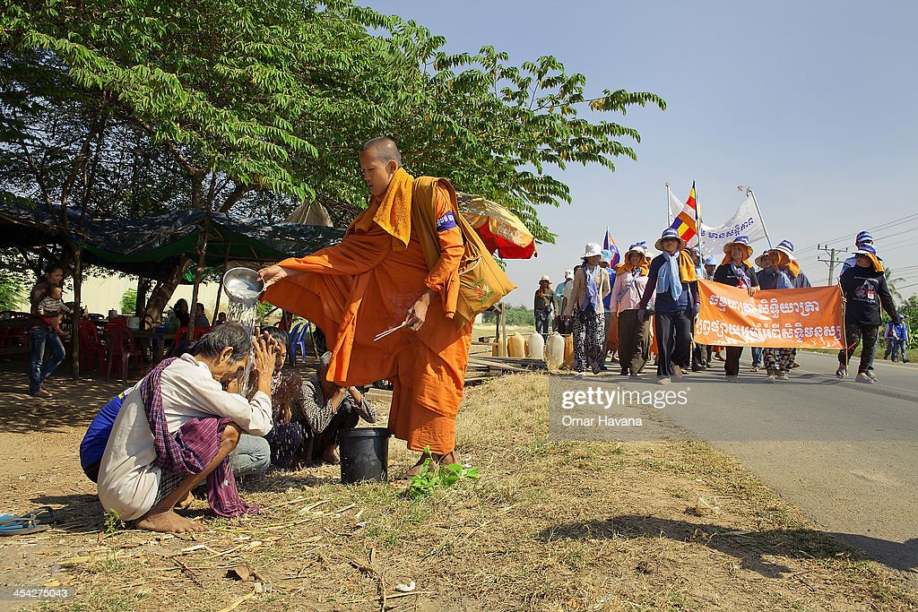 A Buddhist monks blesses bystanders on national road one on December 8, 2013 in Phnom Penh, Cambodia. Over 500 Cambodian monks are marching in protest from December 1 - December 10 as they head to Phnom Penh to take part in coordinated anti-government protests, which will mark the 65th International Human Rights Day. Joining them are communities, associations, networks, federations, unions and NGOs, as well as residents of communities all along the six designated routes.