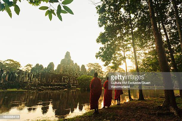 Buddhist monks by temple and lake