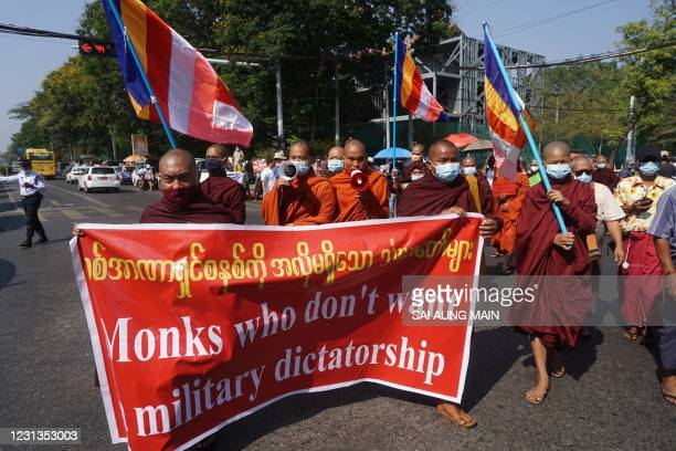 Buddhist monks carry a banner as they take part in a demonstration against the Myanmar military coup outside the Indonesia embassy in Yangon on...