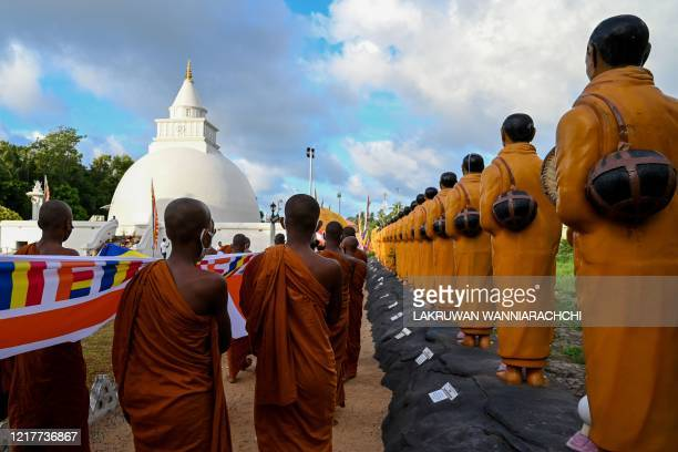 Buddhist monks carry a Buddhist flag to drape it around the stupa in Sri Vidyashanthi Temple in Colombo on June 5 during the Poson Poya religious...