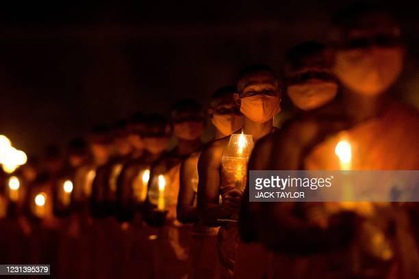 Buddhist monks carry candles during Makha Bucha celebrations at Wat Dhammakaya, north of Bangkok on February 26, 2021.
