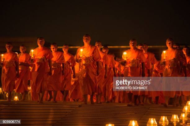 Buddhist monks carry lit candles after evening prayers to mark Makha Bucha Day at Wat Phra Dhammakaya temple near Bangkok on March 1 2018 Makha Bucha...