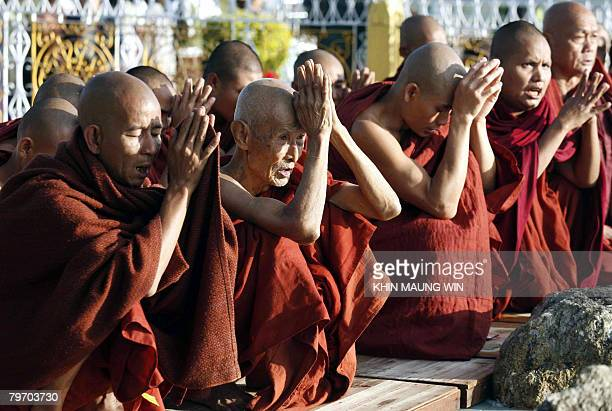 Buddhist monks chant in front of a golden rock at the Kyaikhtiyo Pagoda in Kyaikhto some 170 km northeast of Myanmar's largest city Yangon 25...