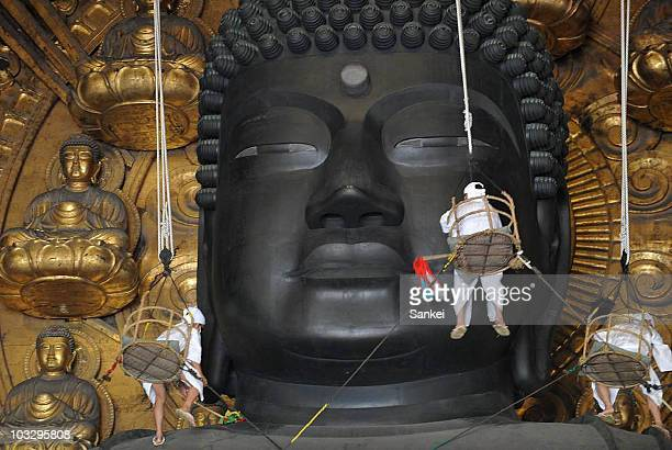 Buddhist monks clean the dust from the 15meterhigh Great Buddha at the Todaiji Temple on August 7 2009 in Nara Japan The Great Buddha which was...