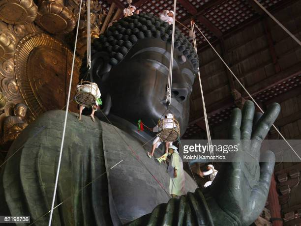 Buddhist monks clean the dust from the 15meterhigh Great Buddha at the Todaiji Temple on August 7 2008 in Nara Japan The Great Buddha which was...