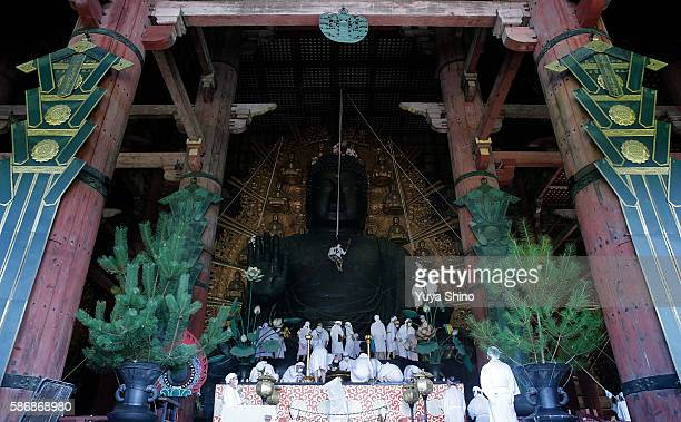 Buddhist monks clean the dust off of 'Daibutsu' or the Great Buddha during the annual cleaning at Todaiji temple on August 7 2016 in Nara Japan The...