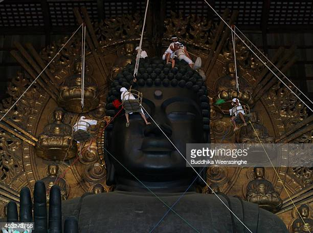 Buddhist monks clean the dust off of the 15meterhigh Great Buddha at the Todaiji Temple on August 7 2014 in Nara Japan About 100 Buddhist monks take...