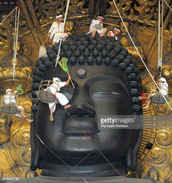 Buddhist monks clean the dust off of the 15meterhigh Great Buddha at the Todaiji Temple on August 7 2011 in Nara Japan About 100 Buddhist monks take...