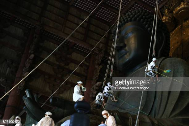 Buddhist monks clean the dust off of the 15meterhigh Great Buddha at Todaiji Temple on August 7 2017 in Nara Japan The Great Buddha of Nara built in...