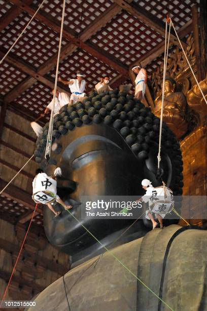 Buddhist monks clean the dust off of the 15meterhigh Great Buddha during the annual cleaning ahead of the Japanese 'Bon' holiday season at Todaiji...