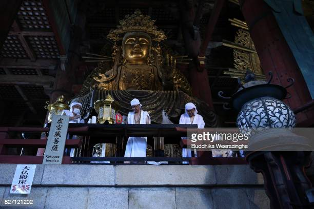 Buddhist monks clean the dust off of the 15meterhigh Great Buddha during the annual cleaning at Todaiji Temple on August 7 2017 in Nara Japan The...