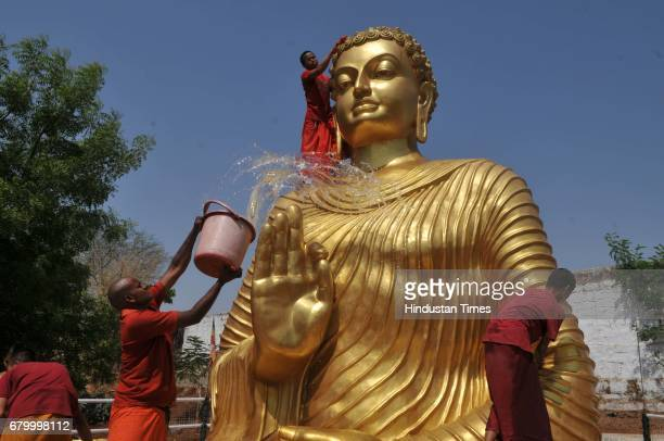 Buddhist monks cleaning and washing Buddha idol ahead of Buddha Purnima at Maitrayi Vihar on May 7 2017 in Bhopal India Buddha Purnima marks the...