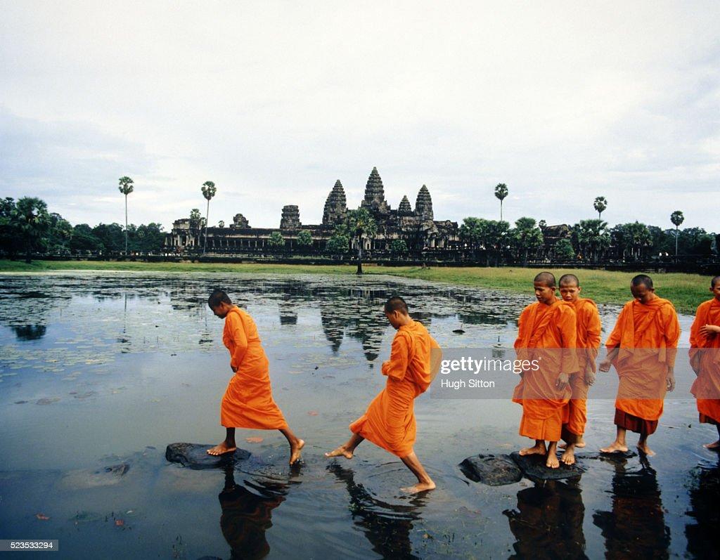 Buddhist Monks Crossing Lake on Rocks : Stock Photo
