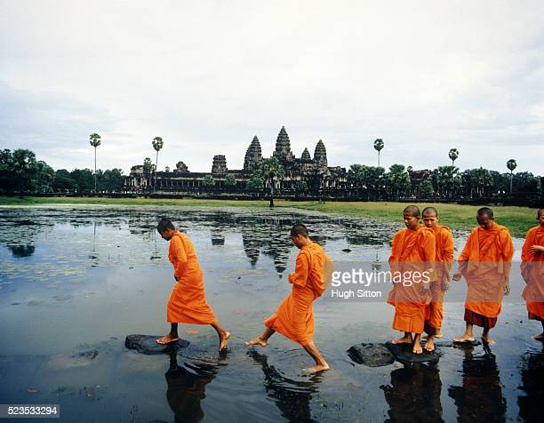 Buddhist Monks Crossing Lake on Rocks