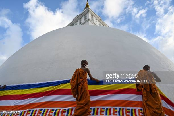 Buddhist monks drape a Buddhist flag around the stupa in Sri Vidyashanthi Temple in Colombo on June 5 during the Poson Poya religious festival Sri...